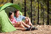 Camping couple in tent sitting looking at view in forest. Campers smiling happy outdoors in forest.