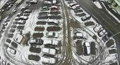 Cars in the parking lot covered with snow, aerial view