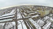 Urban landscape with snow-covered streets on a cloudy day, aerial view