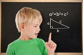 Composite image of cute boy pointing against blackboard