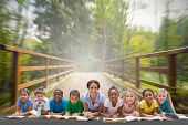 Cute pupils smiling at camera with teacher against bridge with railings leading towards forest