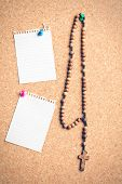 the rosary beads on cork board