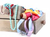 Grey drawer full of multicoloured ribbons and beads on white background isolated