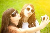 Duckface. Selfie. Two young trendy girls doing selfie. A couple of friends photographing themselves.