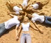 Group young friends enjoying a beach party on vacation. People having fun  against the sea on holidays. Group of happy young people dancing, jumpimg and spraying at the beach on summer sunset.