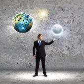Young man in suit holding moon planet in palm. Elements of this image are furnished by NASA