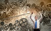 Young strong businessman tearing metal chain with hands