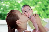 picture of kiddie  - Mother kissing her baby close up, in Thailand
