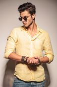 cool fashion model with palms together and sunglasses looking at the camera