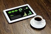 Tablet pc with graphs and cup of coffee on wooden table