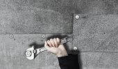 Close up of businessman hand fixing mechanism with spanner