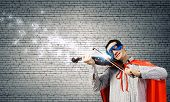 Young man in superhero costume playing violin