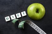 picture of scrabble  - Green apple with measuring tape and scrabble letters on black background - JPG