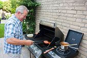 Retired Dutch Senior Man Grilling Hamburgers