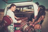 Multi-ethnic hippie couple with guitar packing luggage for a road trip