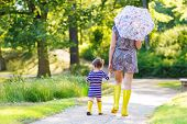 Mother And Little Adorable Daughter In Yellow Rubber Boots
