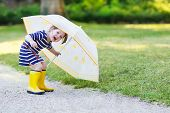 picture of rain  - Adorable little toddler girl having fun with umbrella in yellow rain boots and umbrella in summer park - JPG