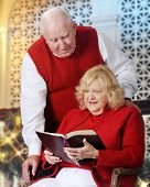 A senior woman reading from the Bible, her husband looking over her shoulder.  They're wearing read and white while in a Christmas-decorated room.