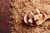 Brown sugar cubes in wooden spoon on crystal sugar background