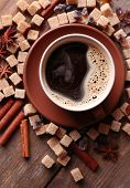 Brown sugar, spices and cup of coffee on wooden background