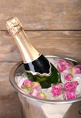 Frozen rose flowers in ice cubes and champagne bottle in bucket, on wooden background
