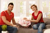 Happy young family sitting at home on sofa with little baby girl, smiling, looking at camera.
