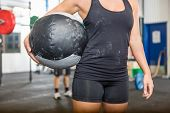 Midsection of female athlete carrying medicine ball at gym