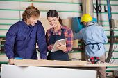 Male and female carpenters using digital tablet together in workshop