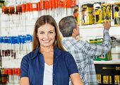 Portrait of beautiful woman smiling with man buying tools in background at hardware store
