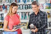 Smiling man and woman paying for flashlight through smartphone in hardware store