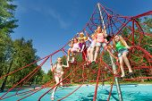 Playful kids sit on red ropes of playground