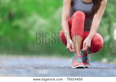 Running shoes - closeup of lady tying shoe bands. Female game wellness runner getting prepared for r