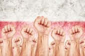 stock photo of labourer  - Poland Labour movement workers union strike concept with male fists raised in the air fighting for their rights Polish national flag in out of focus background - JPG