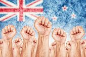 image of labourer  - New Zealand Labour movement workers union strike concept with male fists raised in the air fighting for their rights New Zealand national flag in out of focus background - JPG
