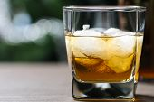 picture of whiskey  - glass with whiskey and ice on wooden table on the background of trees - JPG