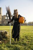 picture of pale skin  - Witch with pale skin hold broom and pumpkin - JPG