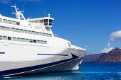 Modern tourist cruise ship sailing on Aegean sea, Santorini island, Greece. Sunny, blue sky.