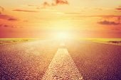 stock photo of long distance  - Long empty asphalt road towards sunset sun - JPG