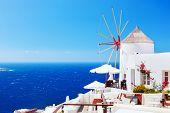 Oia town on Santorini island, Greece. Famous windmills on cliff over the Caldera, Aegean sea.