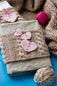 picture of blanket snow  - Two old pads in knitted cover with felt hearts lie next to the coil bright filaments and blanket knitted on blue background - JPG