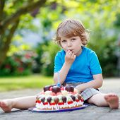 Little Boy Celebrating His Birthday In Home's Garden With Big Cake
