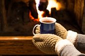 Hot Tea In Hands And Fireplace Background