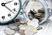 Coins, clock and open glass jar on  a data table