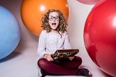 Screaming Curly Teen Girl In Glasses With Wooden Abacus On The Background Of Large Rubber Balls