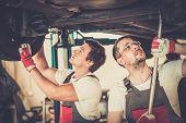 Servicemen checking suspension in a car workshop
