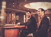 Two fashionable men in suits behind table in a casino