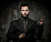 Handsome well-dressed man with walking stick sitting in leather chair