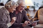 stock photo of wifes  - Elderly husband and wife networking at home - JPG