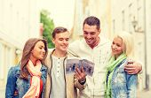travel, vacation and friendship concept - group of smiling friends with city guide exploring town