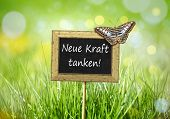 An image of a little chalkboard in the garden with the recharge your power in german language